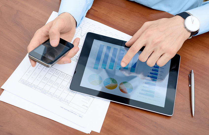 A person in a blue shirt working from his iPhone and iPad.