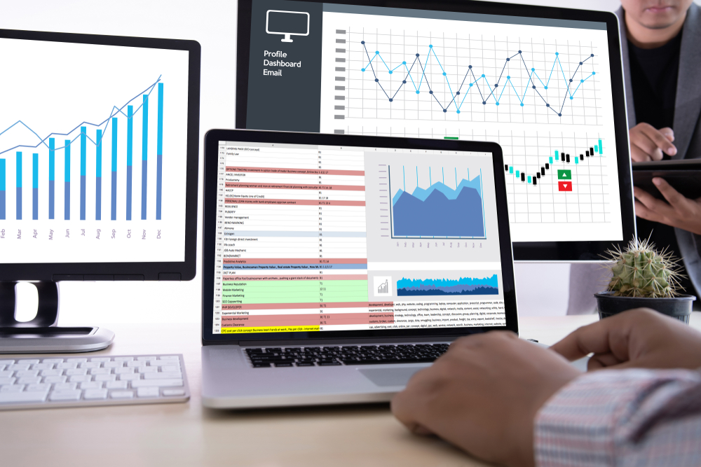 Photograph of three laptop monitors with various graphs and google analytics reports