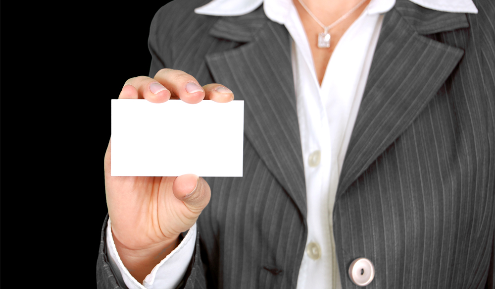 A person in a suit holding a plain white business card.