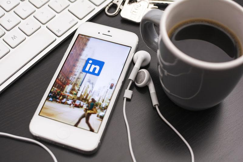 An iPhone loading the LinkedIN app with a cup of coffee resting on a wooden table.