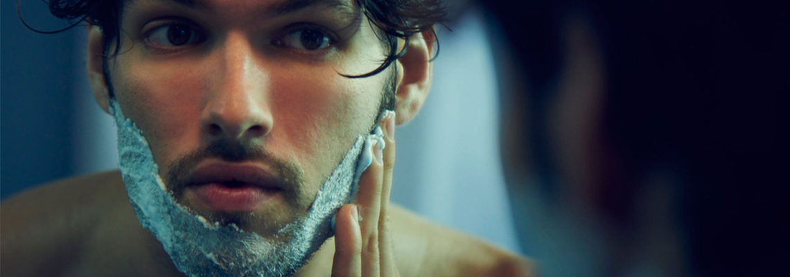 A person placing shaving foam on their beard, preparing to shave.