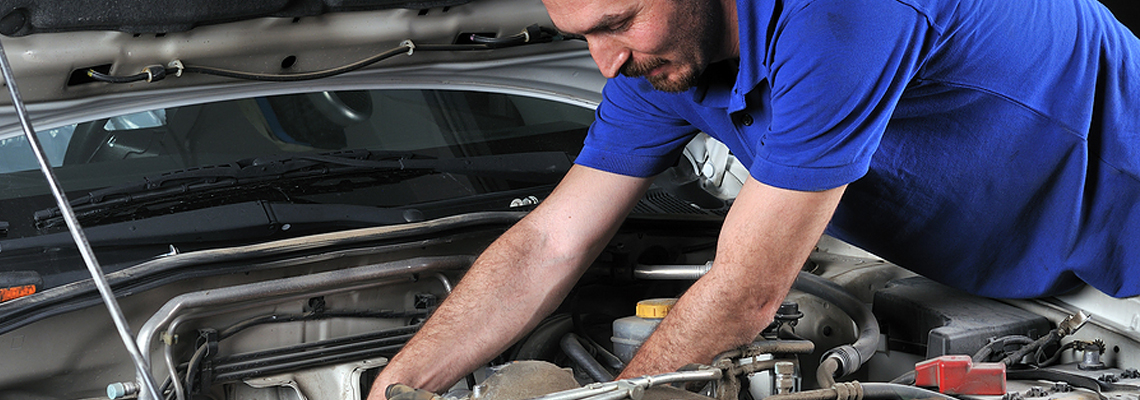 A car mechanic wearing a blue polo while working on fixing the engine to a car.