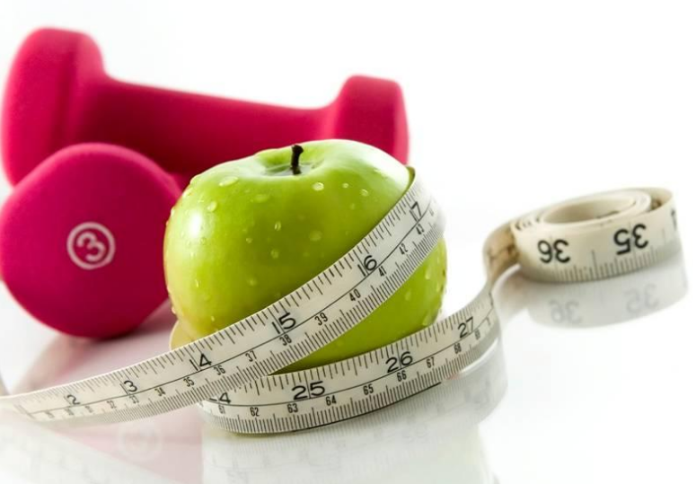 An apple with a measuring tape wrapped around it and red dumbells in the background.