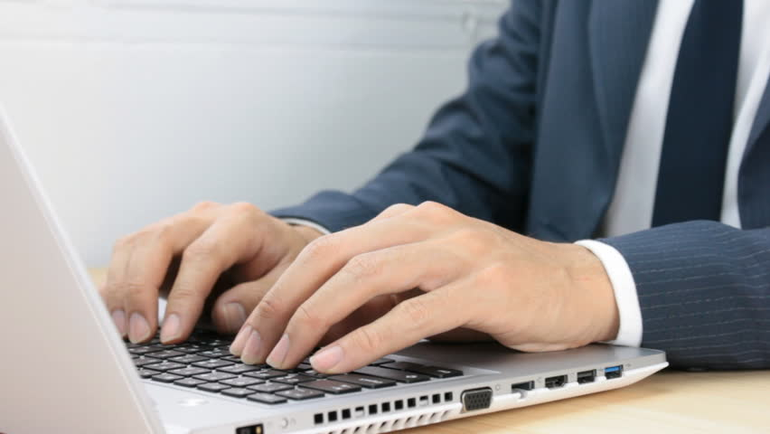 A person in a suit typing on their laptop.