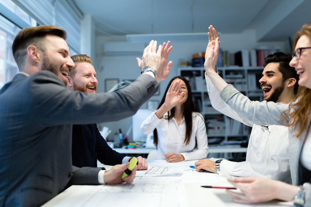 Photograph of business people surrounding a white table high fiving due to winning business contracts