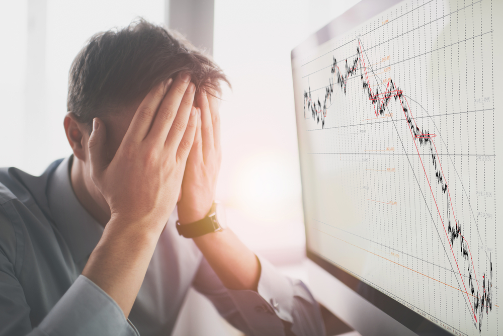 Photograph of an upset business owner next to a chart that is rapidly declining