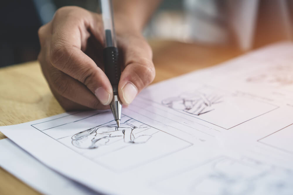 Photograph of man storyboarding video concept by hand