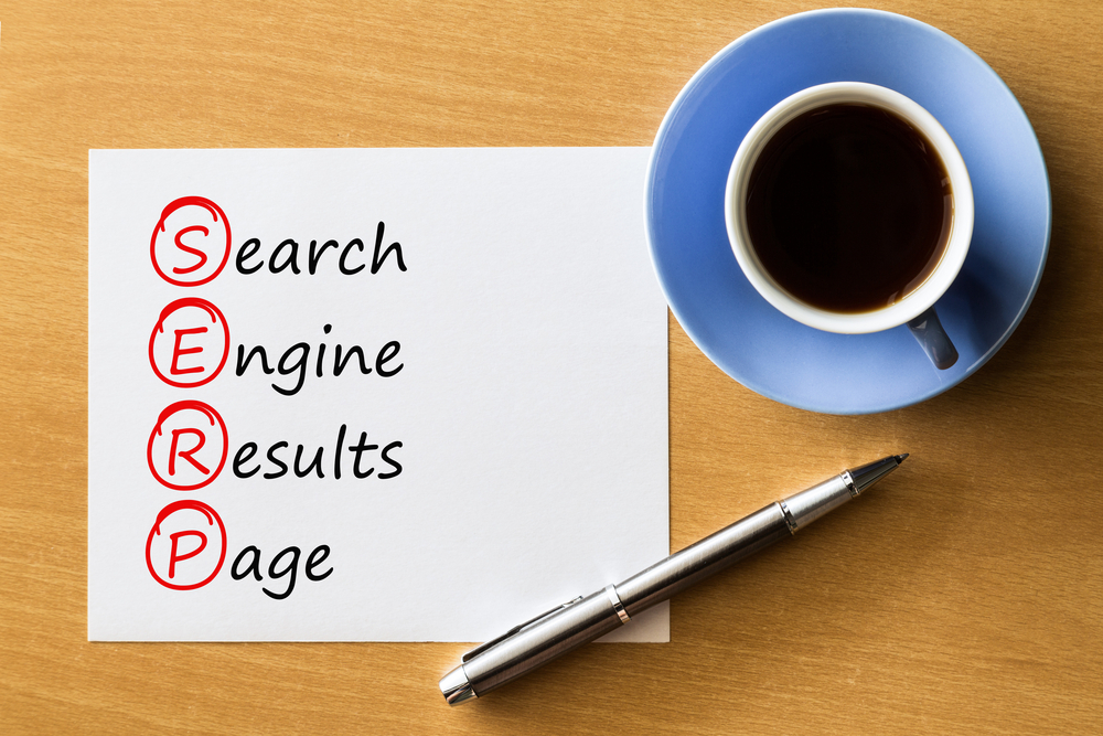 A wooden table with a cup of coffee and a saucer next to a piece of paper showing that SERP stands for; serch engine results page.