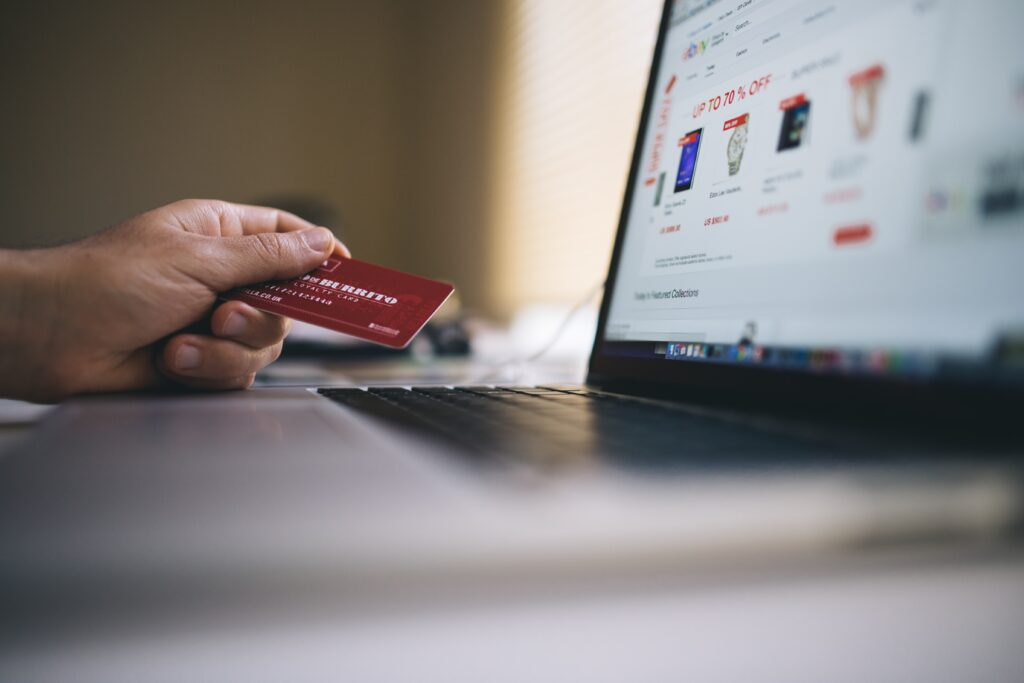 A person holding their credit card while shopping on an e-commerce store on their laptop.