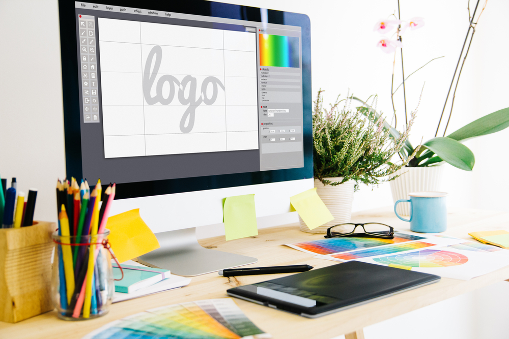 A MacBook laptop with Photoshop is open to design a logo that is within the brand guidelines.