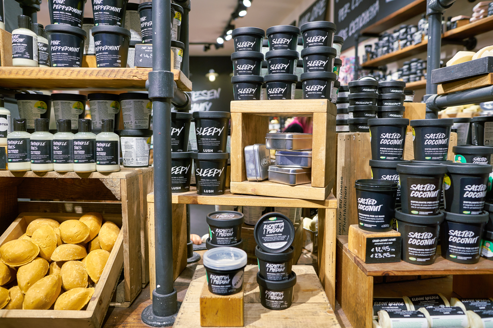 A variety of black pots containing Lush products stacked across various wooden surfaces.