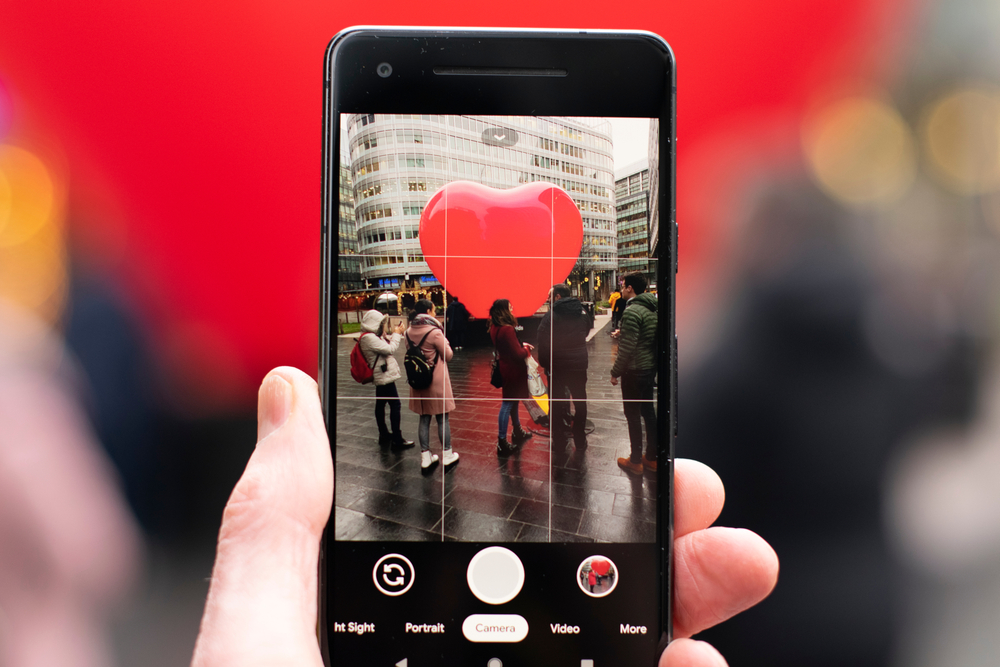 A person taking a photo on their iPhone, using the rule of thirds grid on the camera to take a picture.
