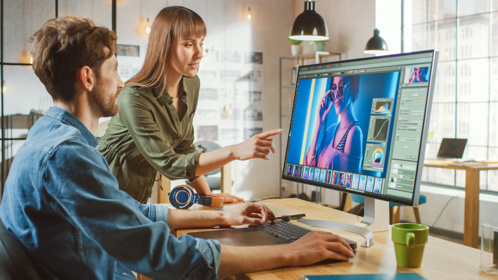 Two graphic designers working on a Photoshop project whilst understanding how to make an animation in photoshop.