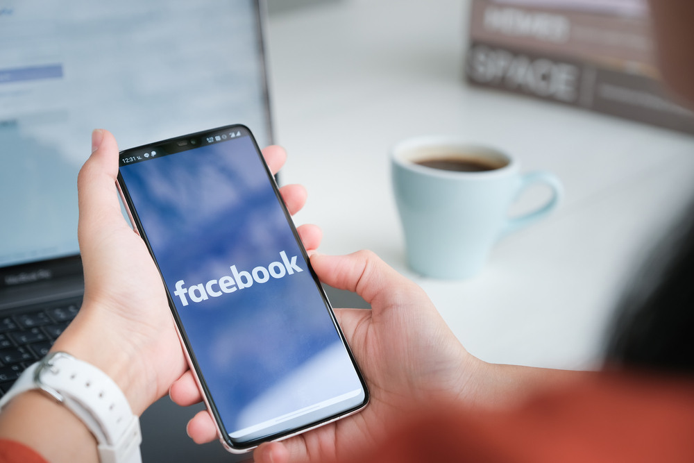 The Facebook app being opened on an iPhone with a social media assistant preparing to schedule a post.