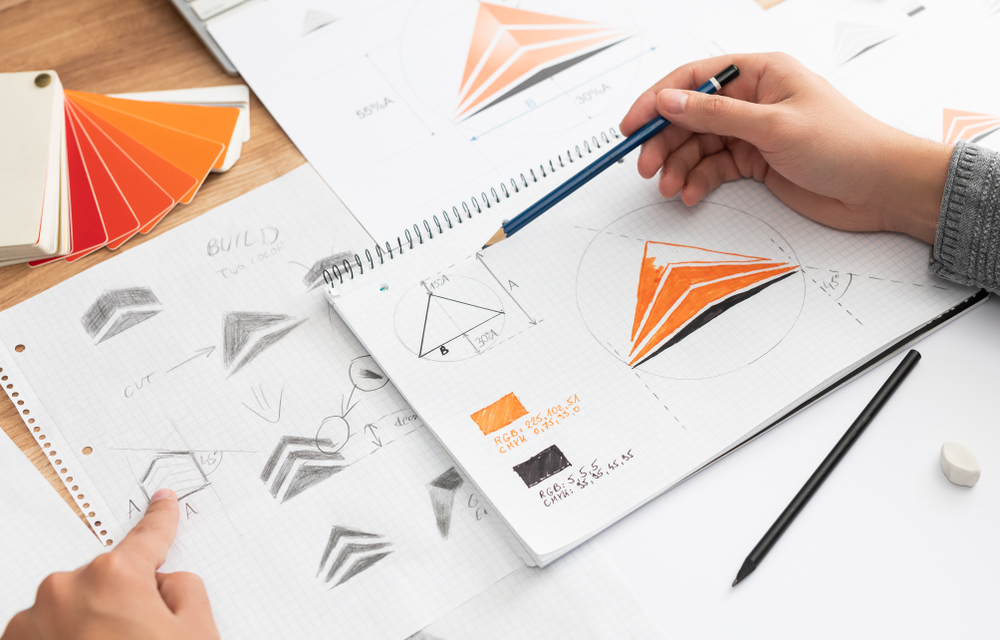 A graphic designer drawing several iterations of a logo to grasp an understanding of their corporate branding.