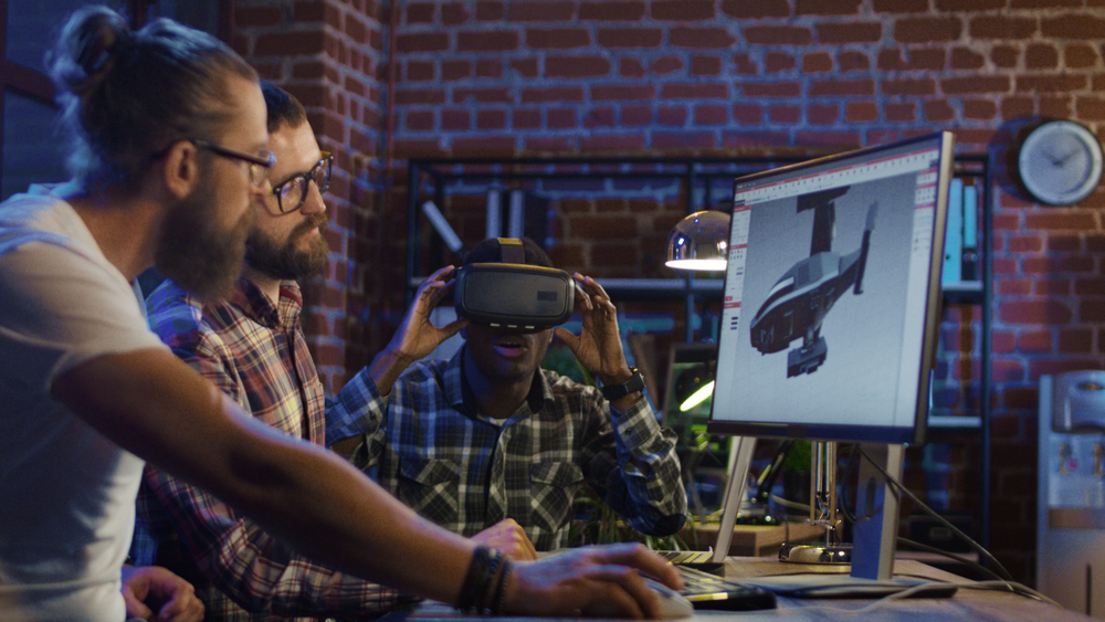 Three graphic designers working on a virtual reality project to showcase how is animation used in advertising.