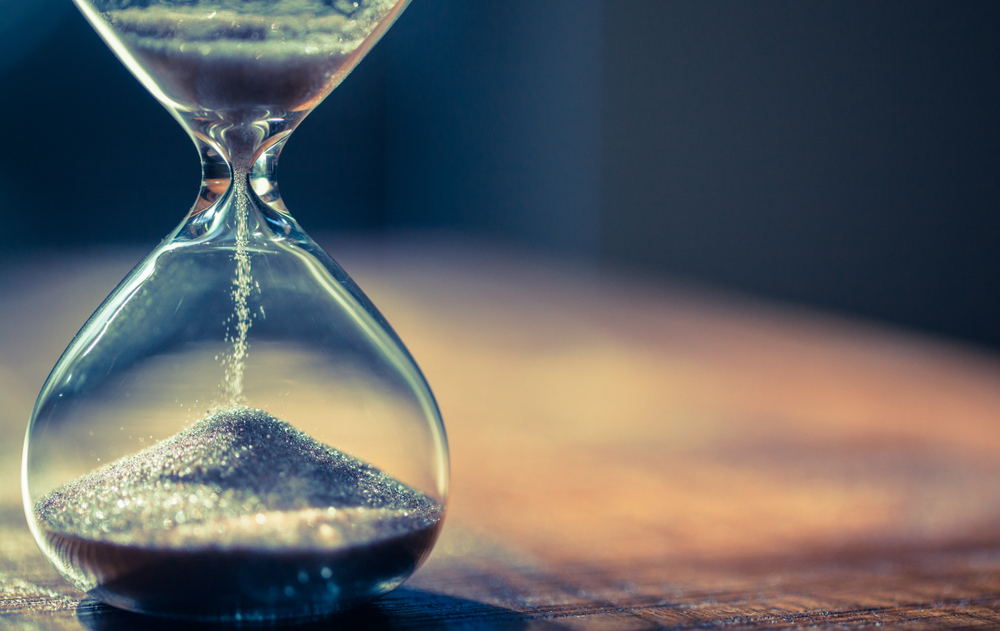 An hourglass on a wooden table to showcase how long does SEO take to work.