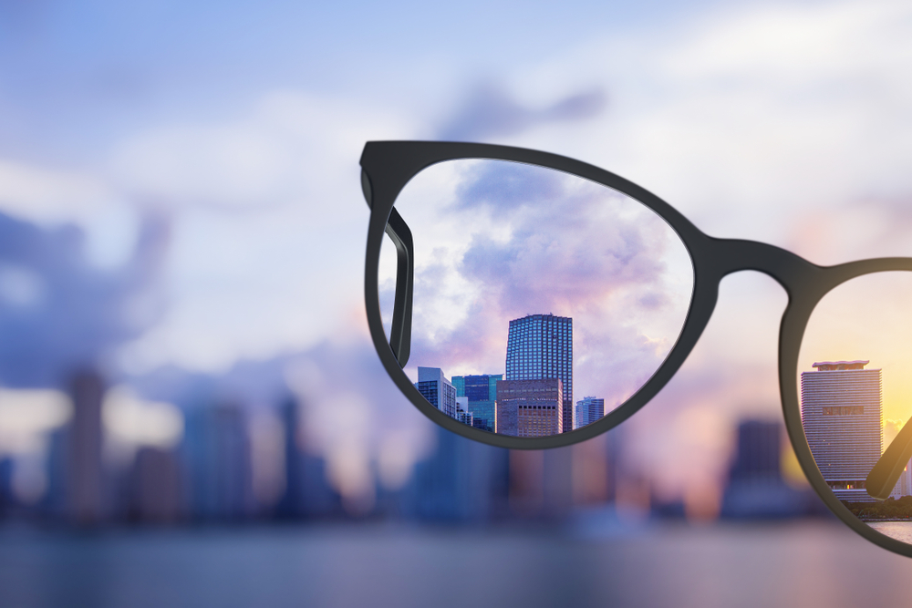 A blurry image overlooking a selection of buildings with a set of glasses in the centre to demonstrate how to increase the resolution of an image without photoshop.