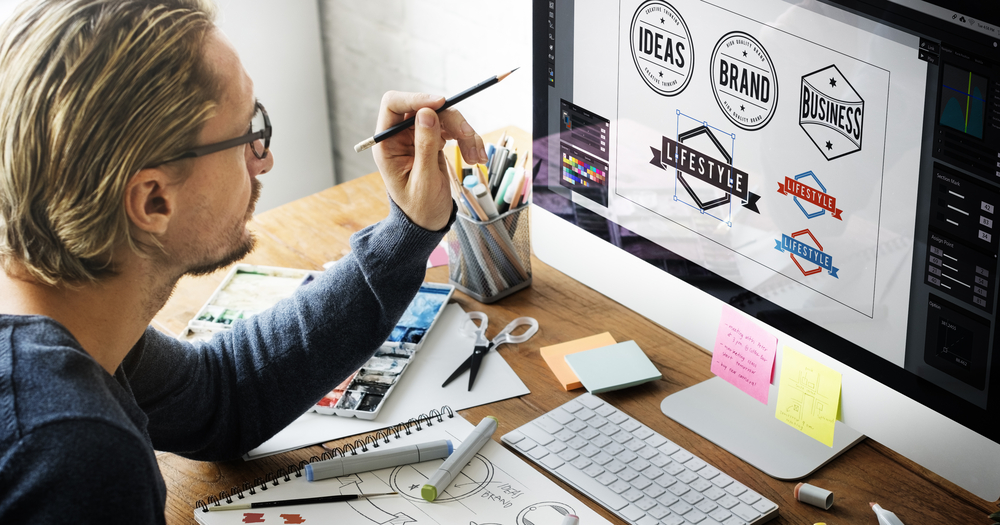 A graphic designer working on their Mac computer, designing multiple logos to grasp an understanding of what is corporate branding.